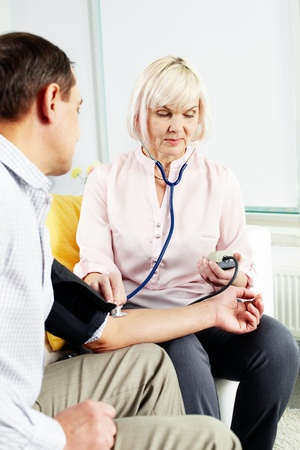 Portrait of mature woman measuring blood pressure of her husband at home Stock Photo - 14726930