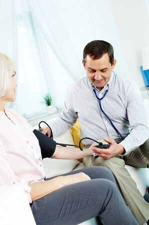 Portrait of mature man measuring blood pressure of his wife photo