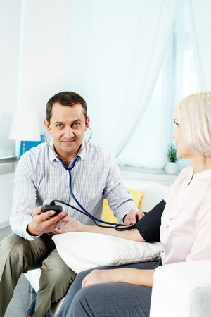 Portrait of mature man measuring blood pressure of his wife and looking at camera Stock Photo - 14726929