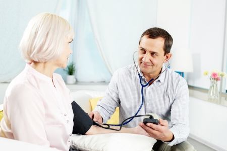 Portrait of mature man measuring blood pressure of his wife and looking at her Stock Photo - 14726887