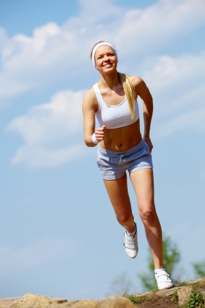 wellness environment: Portrait of happy young woman jogging outside