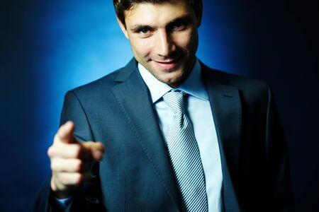 Portrait of handsome male pointing at you and looking at camera in darkness Stock Photo - 14751045