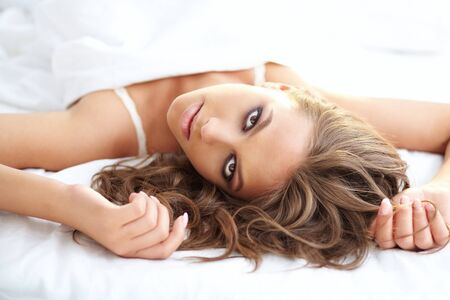 Beautiful woman lying in bed and looking at camera Stock Photo - 14751041
