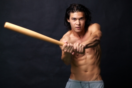 asian abs: Sexy baseball player aiming a blow with a bat
