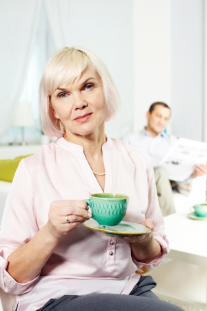 madam: Portrait of mature woman with cup looking at camera on background of her husband Stock Photo