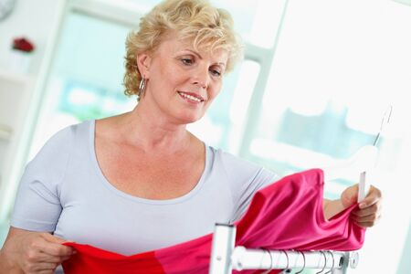 tanktop: Portrait of middle aged woman choosing new tanktop in clothing department Stock Photo