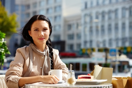 lifestyle looking lovely: Image of pretty female in open air cafe looking at camera in urban environment