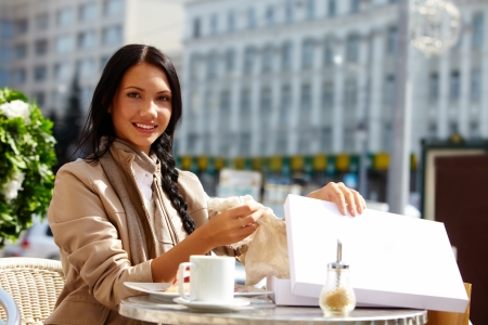 open air: Image of happy female in open air cafe taking out gift out of box outdoors