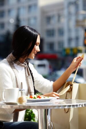 Image of happy female in open air cafe looking at paperbags in urban environment Stock Photo - 14798622