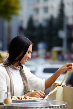 Image of happy female looking at paperbags in urban environment Stock Photo - 14798620