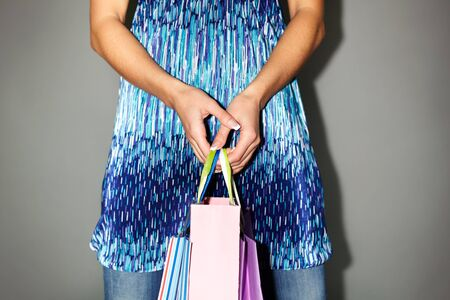 Image of shopaholic hands with three shopping bags photo