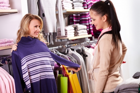 choosing clothes: Image of two pretty girls choosing clothes from new collection in department store