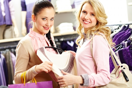 Image of two pretty girls looking at camera with smiles in department store photo