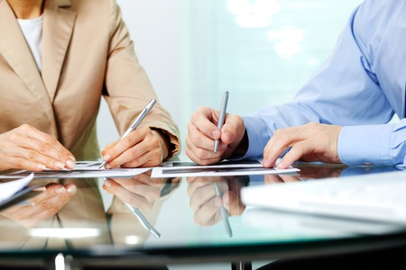 Business people sitting together and making notes at workplace photo