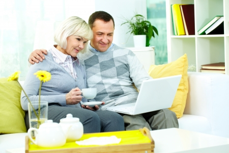 Portrait of mature man and his wife working with laptop at home photo