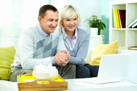 Portrait of mature man and his wife sitting in front of laptop at home and watching movie or online broadcasting Stock Photo - 14838240