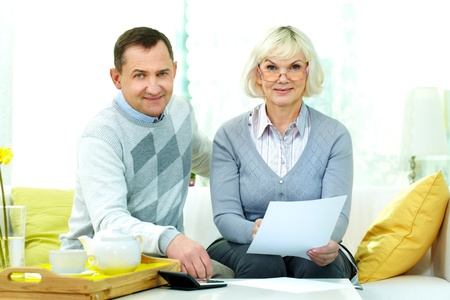 Portrait of mature man and his wife making financial revision at home photo