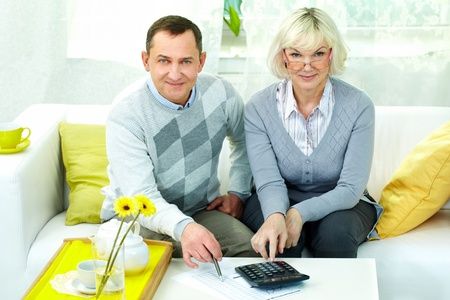 Portrait of mature man and his wife looking at camera while making financial revision at home photo