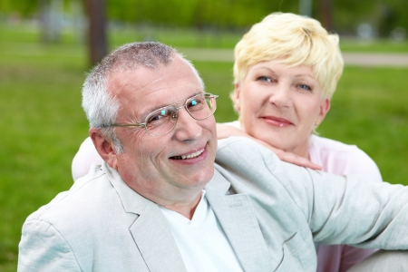Happy mature man looking at camera with his wife on background photo