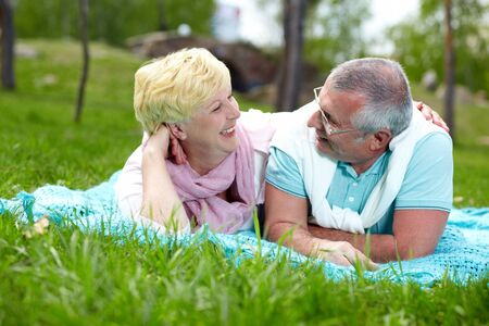 Happy mature couple lying on grass and talking in the countryside photo