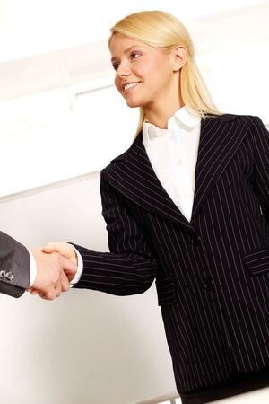 Confident business woman congratulating a business partner and shaking hand with him photo