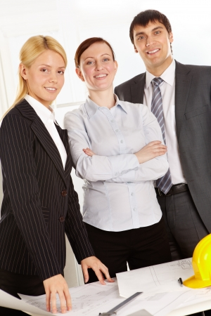Three business people standing at table with plan, looking at camera and smiling photo