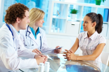 Portrait of confident practitioners consulting patient in hospital photo