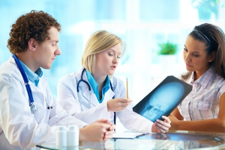 medical attention: Portrait of two doctors and young female patient reading x-ray in hospital Stock Photo