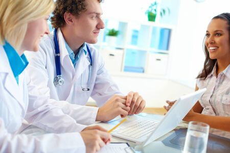 Portrait of confident practitioners and patient communicating in hospital Stock Photo - 14843627