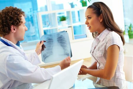Portrait of male doctor showing young female patient x-ray in hospital photo
