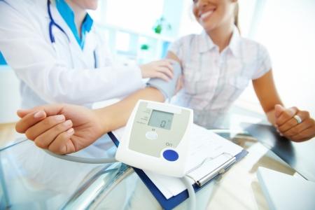 consulta médica: Primer plano de tonómetro brazo por los pacientes durante la medición de la presión arterial en la consulta médica