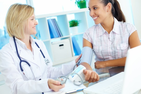 happy doctor woman: Doctor measuring blood pressure of patient at medical consultation Stock Photo