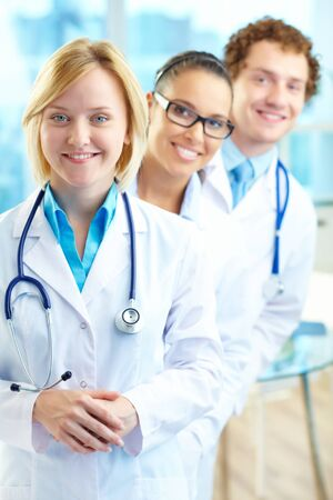 Portrait of three clinicians in white coats looking at camera photo