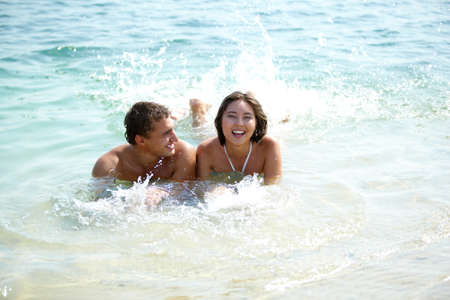 wet girl: Portrait of a happy couple lying in warm water and joyful girl laughing