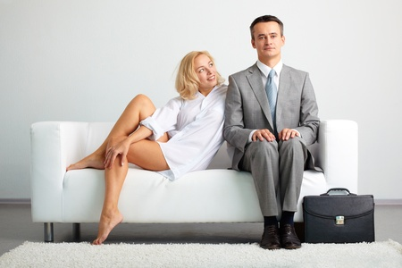 Lovely woman looking at serious businessman while both sitting on sofa photo