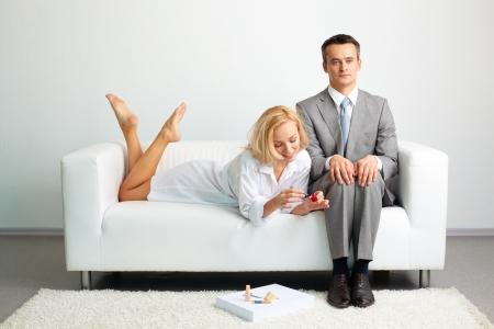 poner atencion: Empresario Tensed tratando de no prestar atenci�n a una mujer sexy haciendo la u�a cercano