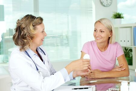 practitioner: Portrait of confident practitioner prescribing vitamins to patient in hospital Stock Photo