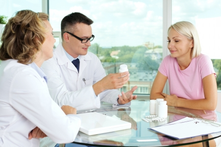 prescribing: Portrait of confident practitioner describing new vitamins to patient in hospital Stock Photo