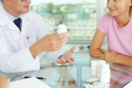 Close-up of male practitioner describing new vitamins to patient in hospital photo