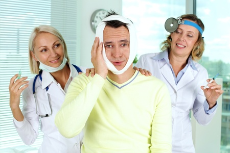 Portrait of two careful female doctors giving first aid to male patient with toothache in hospital Stock Photo - 15185252