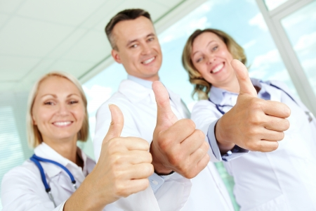 Three clinicians in white coats keeping thumbs up and looking at camera photo