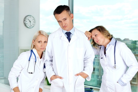 indifferent: Three clinicians in white coats tired after working week Stock Photo