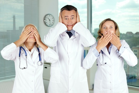 dumb: Three clinicians in white coats covering eyes, mouth and ears