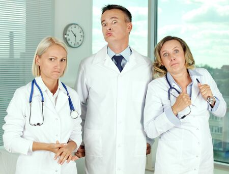 Three clinicians in white coats looking angrily at camera photo
