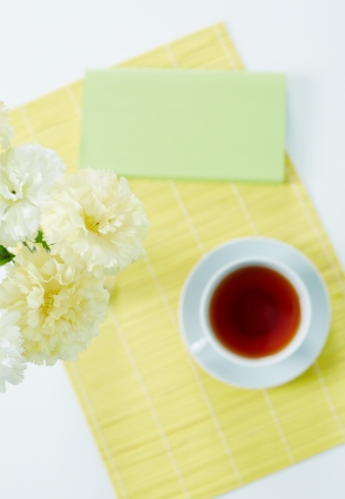 Above angle of white carnations with cup of tea and napkin near by photo