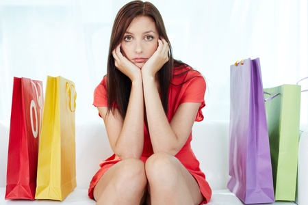 paperbags: Portrait of young stressed brunette surrounded by paperbags Stock Photo