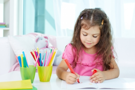girl drawing: Portrait of lovely girl drawing with colorful pencils Stock Photo