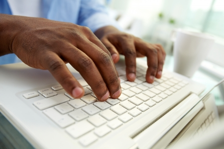 african american ethnicity: Close-up of African man typing on laptop Stock Photo