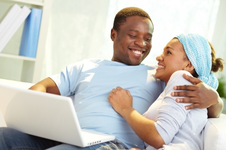 Image of young African couple looking at one another with laptop near by photo