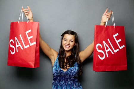 Portrait of joyful brunette showing paperbags photo